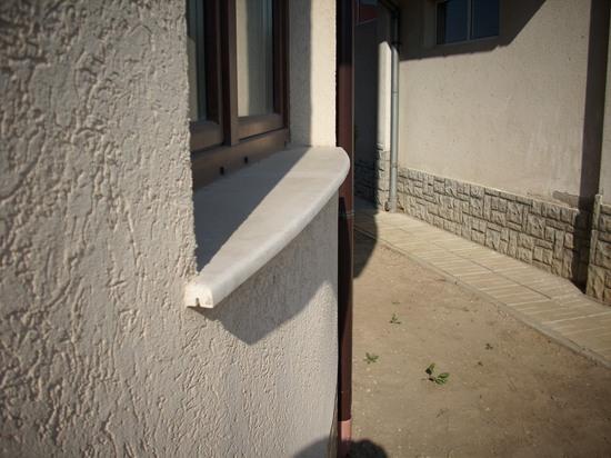 Светъл каменен перваз от външната страна на прозорец