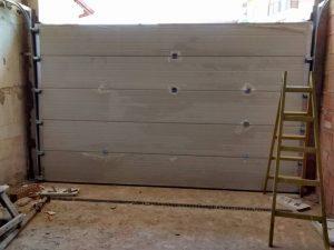 в процес на монтирането на секционна гаражна врата, стълба