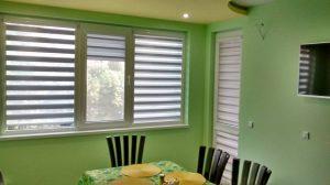Щори ден и нощ монтирани от ДАС Добрич в стая със зелени стени, маса, столове и телевизор
