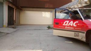Чисто ново монтираната двойна гаражна врата, колата на фирма ДАС Добрич със стълба отгоре и един служител седнал в нея