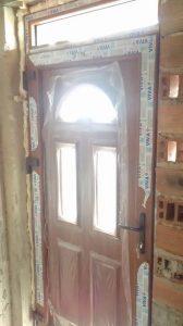 входна врата току що монтирана с 3 прозореца и лепенки по нея