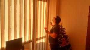 Мъж с чаша пробва новопоставените вътрешни вертикални щори