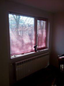 червени хоризонтални алуминиеви щори монтирани на прозорец и винтоверт за монтаж поставен на перваза на прозореца