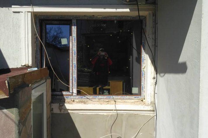 Прозорец дограма на къща сниман от мъж, който се вижда в отражението